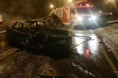 Carro pega fogo após colidir contra muro e motorista foge